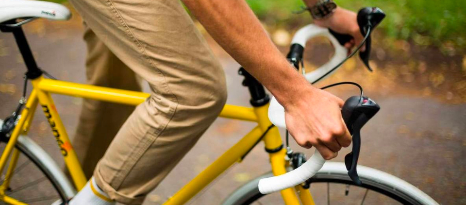 hands of man riding a yellow and white bike